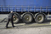 Lorry driver checking his tyres on a London street - Philip Wolmuth - 28-10-2015