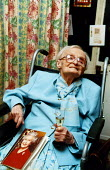 Elderly woman celebrates her 100th birthday, has a card from the Queen, Haringay , North London - Joanne O'Brien - 100,100th,2000s,2003,adult,adults,age,ageing population,Birthday,Birthday Party,Birthdays,bound,Champagne,CHAMPAIGN,cities,city,communities,COMMUNITY,Council Services,Council Services,disabilities,dis