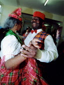 Elderly people dancing Domincan Quadrille at community centre in Haringey, North London - Joanne O'Brien - 2000s,2002,ACE arts culture & entertainment,Active,adult,adults,Afro-Caribbean,age,ageing population,BAME,BAMEs,black,BME,bmes,centre,cities,city,communities,community,Council Services,Council Service