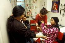 Bengali interpreter (left) working at hospital in East London - Joanne O'Brien - 2000s,2002,adult,adults,asian,BAME,BAMEs,bilingual,Black,BME,bmes,care,cities,city,communicating,communication,diversity,Doctor,DOCTORS,EAL,EFL,ESL,ESOL,ethnic,ethnicity,explaination,FAMILY,FEMALE,for