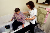 Occupational therapist with client at home, outreach NHS scheme. - Joanne O'Brien - 2000s,2002,assistance,assistant,ASSISTANTS,Bath,Bathing,Bathroom,care,cord,Emergency,FEMALE,Handrail,HEA health,health,HEALTH SERVICES,healthcare,home,job,jobs,LAB LBR work,National Health Service,NHS