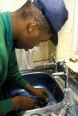 Hackney Council plumber fits new kitchen sink - Joanne O'Brien - 2000s,2002,BAME,BAMEs,black,BME,bmes,BUILDING,BUILDINGS,construction,Construction Industry,council,Council Services,Council Services,direct,diversity,employee,employees,Employment,ethnic,ethnicity,fix