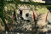 Children playing on swings on Wood Dene estate, Peckham, London - Joanne O'Brien - 2000s,2002,area,child,CHILDHOOD,children,cities,city,Council Services,Council Services,housing,juvenile,juveniles,kid,kids,local authority,London,outdoors,outside,people,play,PLAY AREA,PLAY AREAS,PLAY