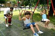 Children play on swings, Kingswood Estate, Southwark, London - Joanne O'Brien - 2000s,2002,BAME,BAMEs,black,BME,bmes,boy,boys,child,CHILDHOOD,children,cities,city,council estate,Council Services,council estate,Council Services,DAD,DADDIES,DADDY,dads,diversity,ethnic,ethnicity,fam