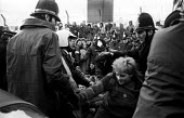Greenham Common, 1982 Women protest against the deployment of US cruise missiles. Police removing women from a road leading into the base. - Joanne O'Brien - 1980s,1982,activist,activists,adult,adults,against,Airbase,airbases,airforce,Anti War,Anti-nuclear,Antiwar,armed forces,arrest,arrested,arresting,blockade,BLOCKADING,CAMPAIGN,Campaign for nuclear disa