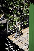 Scaffolder at work, central London - Joanne O'Brien - 2000s,2008,builder,builders,building site,cities,city,Construction Industry,EBF economy,employment,job,jobs,LAB LBR work,London,male,man,manual,men,people,person,persons,scaffold,scaffolder,scaffolder