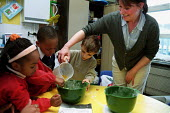 Primary School Children and teacher making a cake mixture - Roy Peters - 12-02-2000