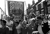 Durham Miners Gala, 1974. Families and children from the pit villages in front of the South Hetton Lodge banner as it is paraded in the annual Big Meeting. - Angela Phillips - 14-07-1974