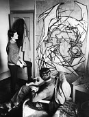 Artist and sculptor, Elisabeth Frink studying one of her paintings in Chelsea, 1953 - Alan Vines - 1950s,1953,abstract,ACE,art,artist,artists,arts,artwork,artworks,cities,city,communicating,communication,conversation,conversations,culture,dialogue,discourse,discuss,discusses,discussing,discussion,d