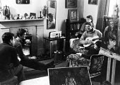 Artists and friends from Chelsea Art School in 1953 enjoying a relaxing moment in the home of painter Ann Irving, sitting on the flowered chair, whose paintings decorate the room. Also in the photogra... - Alan Vines - 1950s,1953,abstract,ACE,art,artist,artists,arts,cities,city,communities,community,culture,drawing,Elisabeth Frink,EMOTION,EMOTIONAL,EMOTIONS,enjoying,ENJOYMENT,female,friend,friends,fun,funny,guitar,H