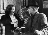 Couple drinking together in a Chelsea pub in 1953. - Alan Vines - &,1950s,1953,adult,adults,alcohol,and,bar,BARS,beer,beers,cigarette,CIGARETTES,cities,city,conversation,Couple,COUPLES,drink,drinker,drinkers,drinking,drinks,fag,female,funny,half,hat,hats,humor,humor