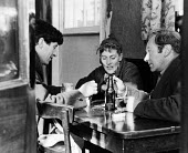 Sculptor, Kenneth Armitage on left, talking in a Chelsea pub with fellow sculptor, Lynn Chadwick, on right, and his wife, writer, Anne Secord, 1953. - Alan Vines - &,1950s,1953,ACE,alcohol,art,artist,artists,arts,beer,bottle,BOTTLES,cities,city,communicating,communication,conversation,conversations,culture,dialogue,discourse,discuss,discusses,discussing,discussi
