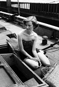 Young woman enjoying the sun on a houseboat moored on the River Thames at Chelsea in 1953. - Alan Vines - 25-03-1953