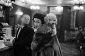 Well dressed woman with her pet poodle in a Mayfair bar in London, 1959. - Alan Vines - 09-12-1959