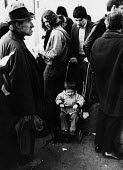 Small boy in pushchair crying as his father visits the Unemployment Exchange, Islington, 1977. - Bob Appleton - 1970s,1977,agency,and,boy,boys,child,CHILDHOOD,children,cities,city,cry,crying,DAD,DADDIES,DADDY,DADS,demasculated,demasculation,employee,employees,Employment,Exchange,families,FAMILY,father,FATHERHOO