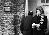 Woman emerges from the Unemployment Exchange in Islington, London, 1977 with her unemployment benefit. - Bob Appleton - 1970s,1977,benefit,benefit office,benefits,cities,city,dole,employee,employees,Employment,Exchange,female,Islington,job,jobless,jobs,jobseeker,jobseekers,lbr,line,London,male,man,Marginalised,men,neet