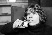 Richard Branson 19 year old editor of Student magazine, eating an apple, London. - Bente Fasmer - 1960s,1969,adolescence,adolescent,adolescents,Apple,Branson,businessman,businessmen,cities,city,core,eating,EBF,Economic,Economy,food,FOODS,healthy,magazine,MAGAZINES,male,man,men,people,person,person