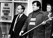 John Tyndall, left, and Martin Webster, with pole, leading members of the National Front, 1976 Election poster for Andrew Fountaine in the Coventry North West byelection, Coventry - Dave Evans - 28-02-1976