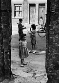 Children of miners playing in an unknown pit village in the north east of England, Prob Easington, 1948. .... - Elizabeth Chat - 1940s,1948,capitalism,capitalist,child,CHILDHOOD,children,Coal Industry,Coal Mine,coalindustry,collieries,colliery,extracting,female,females,girl,girls,Industries,industry,juvenile,juveniles,kid,kids,