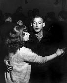 Off-duty American GIs from Burtonwood USAF airbase dancing with local women at the Broadway Club in Warrington.The airbase was reopened in 1948 to support the Wests Cold War effort through the mainten... - Elizabeth Chat - 1940s,1949,ACE,Air,Air force,aircraft,airforce,american,americans,armed forces,at,boyfriend,BOYFRIENDS,Cheshire,club,clubs,culture,dance,dancer,dancers,dancing,drink,drinker,drinkers,drinking,drinks,e