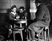 Off-duty American GIs from Burtonwood USAF airbase drinking with a local woman on a Saturday lunch-time in a pub in nearby Warrington. The airbase was reopened in 1948 to support the Wests Cold War ef... - Elizabeth Chat - 1940s,1949,Air,Air force,aircraft,airforce,american,americans,armed forces,bar,BARS,beer,beers,bottle,bottles,boyfriend,BOYFRIENDS,Cheshire,communicating,communication,conversation,conversations,dialo