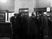 Off-duty American GIs from Burtonwood USAF airbase chatting with a local woman, as British men stand drinking beside them, in a public house in Warrington. The airbase was reopened in 1948 to support... - Elizabeth Chat - 1940s,1949,Air force,air forces airforce,aircraft,Airforce,alcohol,american,americans,armed forces,bar,BARS,beer,boozer,Cheshire Lancashire,communicating,communication,conversation,conversations,dialo