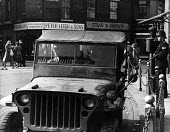 American Jeep manned by military police from the Burtonwood USAF airbase on the streets of nearby Warrington, while a British policeman telephones in to his station. The airbase was reopened in 1948 t... - Elizabeth Chat - 1940s,1949,adult,adults,Air,Air force,aircraft,airforce,american,americans,armed forces,AUTO,AUTOMOBILE,AUTOMOBILES,AUTOMOTIVE,car,cars,Cheshire,CLJ,Force,GI,GIs,jeep,joint,Lancashire,Law,leave,male,m