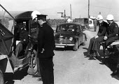 American and British policemen jointly check vehicles leaving the Burtonwood USAF airbase near Warrington. The airbase was reopened in 1948 to support the Wests Cold War effort through the maintenance... - Elizabeth Chat - 1940s,1949,adult,adults,Air,Air force,aircraft,airforce,american,americans,armed forces,AUTO,AUTOMOBILE,AUTOMOBILES,AUTOMOTIVE,car,CARS,check,checking,checkpoint,Cheshire,CLJ,Force,GI,GIs,jeep,joint,L