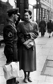 Off-duty American GI from Burtonwood USAF airbase shopping with his wife in nearby Warrington. The airbase was reopened in 1948 to support the Wests Cold War effort through the maintenance and overhau... - Elizabeth Chat - 1940s,1949,Air,Air force,aircraft,airforce,american,americans,armed forces,bought,buy,buyer,buyers,buying,Cheshire,Cold War,commodities,commodity,communicating,communication,consumer,consumers,convers
