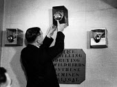 Bird Fanciers' show held in a London pub on a Sunday morning in the early 1950's. Fixing cages to the wall for judging. The sign reads: 'The selling and buying of wild birds on these premises is illeg... - Elizabeth Chat - 11-07-1952