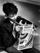 Boy plays with his pet cat in a box as he waits for it to receive treatement in a Mobile Dispensary For Sick Animals of The Poor, London, 1952 - Elizabeth Chat - ,1950s,1952,animal,animals,attention,box,boxes,boy,boys,care,carer,carers,cat,cats,child,childcare,CHILDHOOD,CHILDMINDING,children,cities,city,Dispensary,domestic,early years,EMOTION,EMOTIONAL,EMOTION