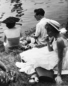 The idle rich at play at the Henley Regatta in an early 1950s summer. .... - Felix H. Man - 1950s,1951,adult,adults,AFFLUENCE,AFFLUENT,Bourgeoisie,class,couple,COUPLES,eat,eating,eating food,elite,elitism,England,EQUALITY,female,food,FOODS,high,high income,income,INCOMES,INEQUALITY,ladies,la