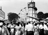 The idle rich at play in the fairground at the Henley Regatta in an early 1950s summer. .... - Felix H. Man - 1950s,1951,AFFLUENCE,AFFLUENT,Big,Bourgeoisie,class,elite,elitism,Enclosure,England,enjoying,enjoyment,EQUALITY,fairground,fun,Funfair,Helter,high,high income,income,INCOMES,INEQUALITY,leisure,LFL,LIF