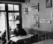 Man drinking in a cafe with advertisements on the walls for the French National Lottery, France, Easter, 1949 - Ina Bandy - 13-04-1949