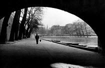 Belgian writer, Georges Simenon walking by the River Seine, Paris, 1947. - Inge Morath - 1940s,1947,ACE,arts,author,authors,Belgian,cafe,cafes,catering,cities,city,culture,eu,Europe,european,europeans,eurozone,Fiction,france,french,Georges,Jules Maigret,male,man,men,Paris,people,person,pe