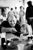 Striking miners and their families enjoying lunch provided by volunteers -mainly miners wives - supporting their dispute. Here a miner helps a young girl eat her lunch at the Kersley Food Kitchen, adj... - John Harris - 04-07-1984