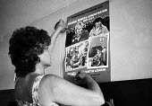Woman volunteer puts up a poster at the Kersley Food Kitchen for striking miners & their families, adjacent to Kersley Colliery near Coventry. advertising the forthcoming National Women's Demonstratio... - John Harris - 04-07-1984