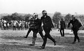 Riot police, some with shin pads on the outside of their uniform, and with batons drawn advance towards miners during violent clashes between miners and riot police officers on the picket lines at the... - John Harris - 18-06-1984