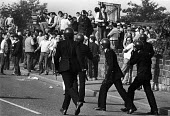 Riot police with batons drawn advacne towards miners during Violent clashes between miners and riot police officers on the picket lines at the Orgreave coking plant during the miners strike Photograph... - John Harris - 18-06-1984