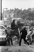 Battle of Orgreave. Bare-chested miners holds up his hand to try and protect himself from advancing riot police officer with baton drawn during violent clashes between miners and riot police officers... - John Harris - 18-06-1984