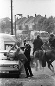 Battle of Orgreave. Bare-chested miners holds up his hand to try and protect himself from riot police officer with baton drawn during violent clashes between miners and riot police officers on the pic... - John Harris - 18-06-1984