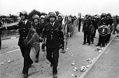 Riot police taking up their positions during violent clashes between miners and riot police officers on the picket lines at the Orgreave coking plant during the miners strike - John Harris - 1980s,1984,adult,adults,Battle of Orgreave,CLJ,DISPUTE,disputes,force,INDUSTRIAL DISPUTE,march marching,MATURE,member,member members,members,MINER,miners,MINER'S,miners strike,miners' strike,miners st