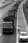 Lorries fitted with grilles and escorted by police vehicles in a convoy carry coal along the motorway from Llanwern to Port Talbot steelworks during the Miners Strike, South Wales - John Harris - 01-08-1984