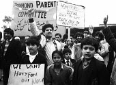 Asian parents & pupils ^No Confidence^ protest at Drummond School in Bradford in the mid 1980's, a demonstration against Headteacher, Ray Honeyford, who the Asian community perceived as making racist... - John Harris - 1980s,1985,activist,activists,against,anger,angry,Asian,BAME,BAMEs,banner,banners,bigotry,BME,bmes,boy,boys,CAMPAIGN,campaigner,campaigners,CAMPAIGNING,CAMPAIGNS,child,CHILDHOOD,children,cities,city,c