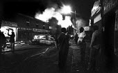 Older men look on as fires burn in the distance during the riot in Handsworth. Debris are scattered across the streets as firefighters (left) arrive to fight the flames. - John Harris - ,1980s,1985,activist,activists,adult,adults,AUTO,AUTOMOBILE,AUTOMOBILES,AUTOMOTIVE,BAME,BAMEs,Black,BME,bmes,Burnt Out,CAMPAIGN,campaigner,campaigners,CAMPAIGNING,CAMPAIGNS,car,cars,cities,city,confli