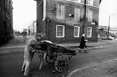 Run down area of Liverpool with boarded up housing, winter, Vauxhall, 1985. - John Harris - 1980s,1985,area,cart,EBF,Economic,Economy,EQUALITY,excluded,exclusion,hand,HARDSHIP,housing,impoverished,impoverishment,INEQUALITY,Liverpool,Marginalised,people,poor,poverty,precariat,precarious,Scrap