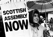 Woman holding banner calling for a Scottish Assembly on a Festival For Democracy march in Glasgow, Scotland, 1987. - John Harris - 1980s,1987,activist,activists,Assembly,banner,BANNERS,campaign,campaigner,campaigners,campaigning,CAMPAIGNS,Democracy,DEMONSTRATING,demonstration,DEMONSTRATIONS,devolution,FEMALE,Festival,FESTIVALS,Gl