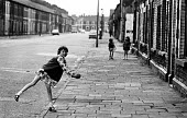 Children walking and playing on the run-down streets of Splott in Cardiff in the mid 1970's - John Sturrock - 1970s,1975,ball,balls,child,CHILDHOOD,children,cities,city,conditions,EQUALITY,excluded,exclusion,female,females,game,games,girl,girls,HARDSHIP,house,houses,housing,Housing Estate,impoverished,impover