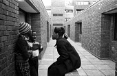 Children resident on the Hindrey Estate in east London chat together on the walkways of the council estate - John Sturrock - 1970s,1976,adolescence,adolescent,adolescents,BAME,BAMEs,black,BME,bmes,boy,boys,child,CHILDHOOD,children,cities,city,communicating,communication,conditions,conversation,conversations,council,dialogue