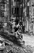 Young boys playing together in the run down Maryhill district of Glasgow in the summer of 1976. - John Sturrock - ,1970s,1976,bleak,boy,boys,building,buildings,child,CHILDHOOD,children,cities,city,clearance,CLEARENCE,collapsed,conditions,council estate,council services,council estate,council services,damage,damag
